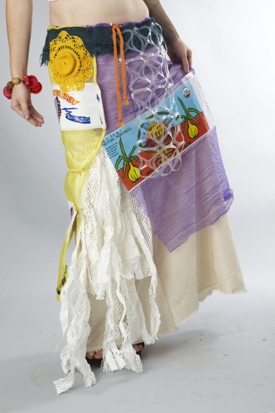 Anya Caskey – Anya is wearing a white paper bodice and a lovely long skirt embellished with found bits of yarn, left over fabric trimmings, grapefruit & orange mesh grove bags and a few other things. Her skirt is basically a trashion fashion collage piece. Her neck is adorned with mini mesh bags from cheese & fruit.