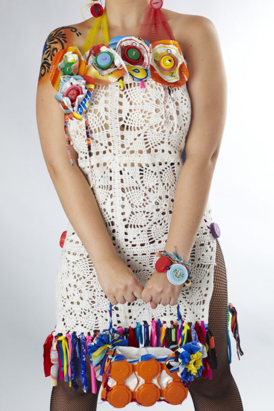 This little dress is trimmed at the bust line with colorful flowers made from laundry pod bags like Tide, foil from yogurt containers & plastic bottle caps drilled to be buttons. The sheath dress is made from crocheted squares Sue's mother found at a garage sale and fringed at the bottom with scraps left over from a swimsuit manufacturer. — with Cassidy Brooks