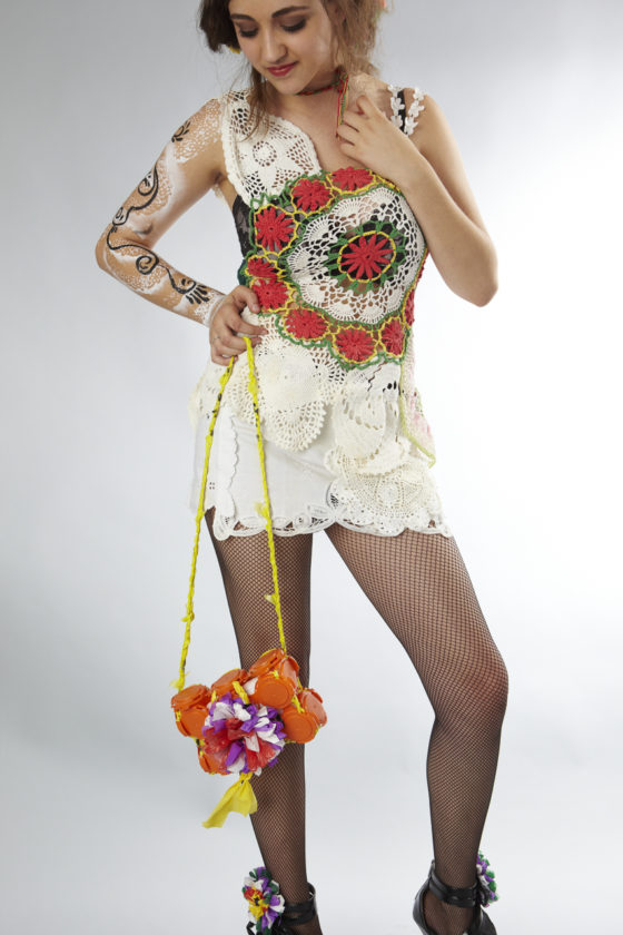 Taylor's dress is assembled from vintage doilies found at garage sales and thrift stores.  Carrying a handbag made from Jai-Alai caps from Tampa Brewing Company stitched together with plarn and adorned with trash flowers. — with Taylor Finke